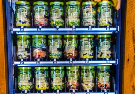 The consumer can see all the salads neatly arranged in a row. All the salads come in reusable plastic jars.