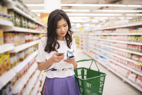 Woman in supermarket with Tetra Prisma Aseptic carton